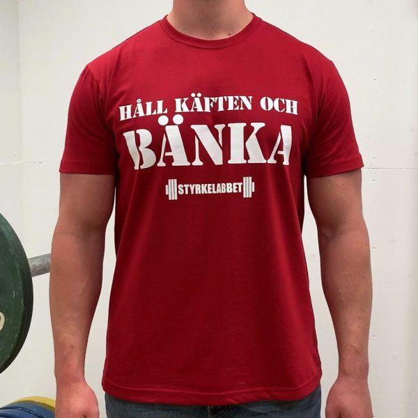 Daniel visar upp t-shirten i färgen röd